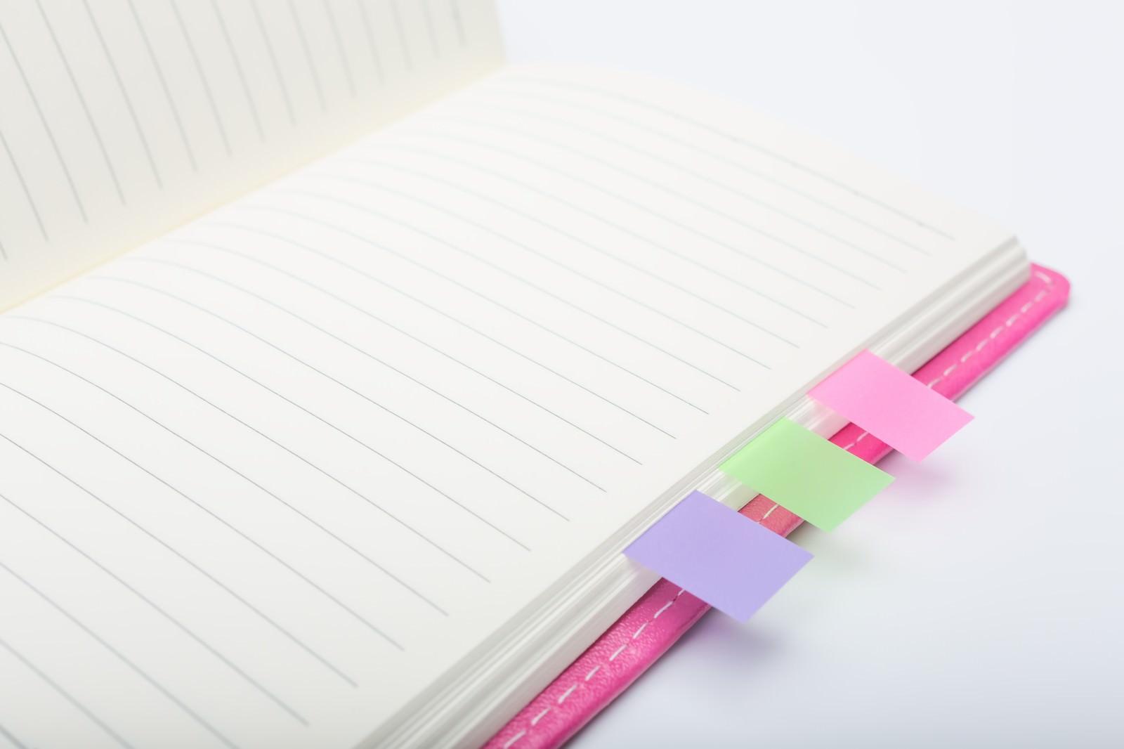 「ピンクの手帳とカラーの付箋」の写真