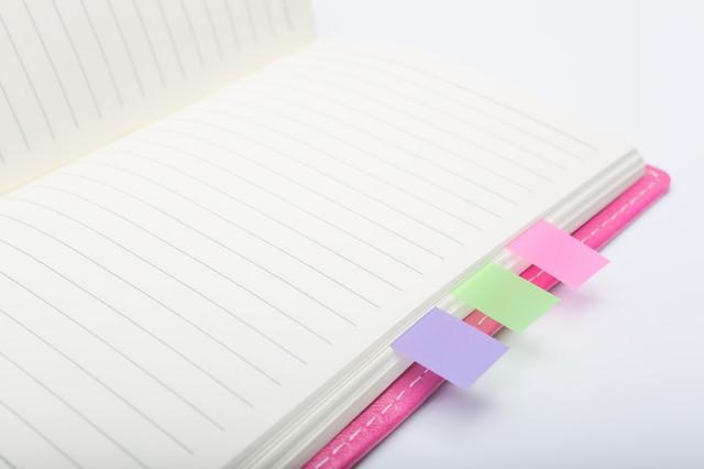 ピンクの手帳とカラーの付箋の写真