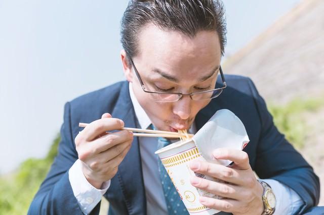カップラーメンをすすり食らうビジネスマン(ドイツ人ハーフ)の写真