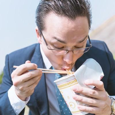 「カップラーメンをすすり食らうビジネスマン(ドイツ人ハーフ)」の写真素材