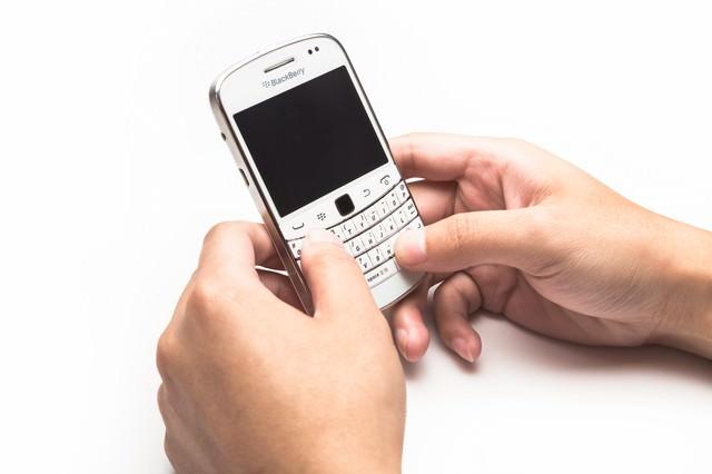 BlackBerryを両手で操作するの写真