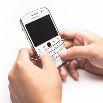 「BlackBerryを両手で操作する」の写真素材