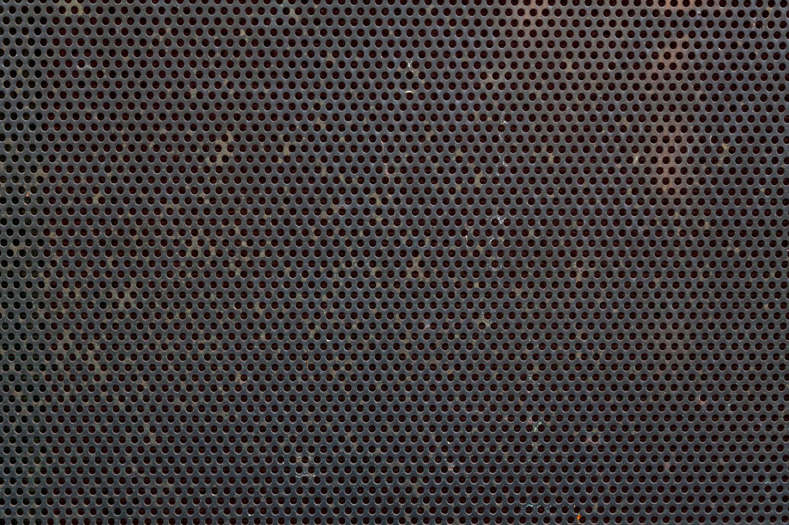 「錆びた丸型の穴が空いたメッシュ金属(テクスチャー)」の写真