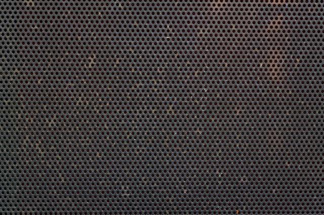 錆びた丸型の穴が空いたメッシュ金属(テクスチャー)の写真
