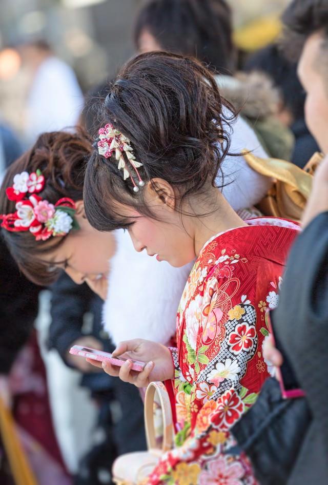 成人式の着物姿でスマートフォンをいじる女性の写真