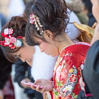 「成人式の着物姿でスマートフォンをいじる女性」の写真素材
