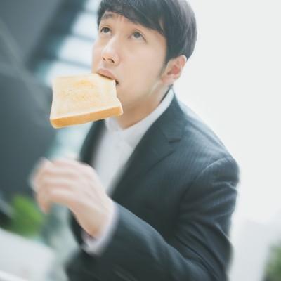 「トーストを咥え颯爽と出社するビジネスパーソン」の写真素材