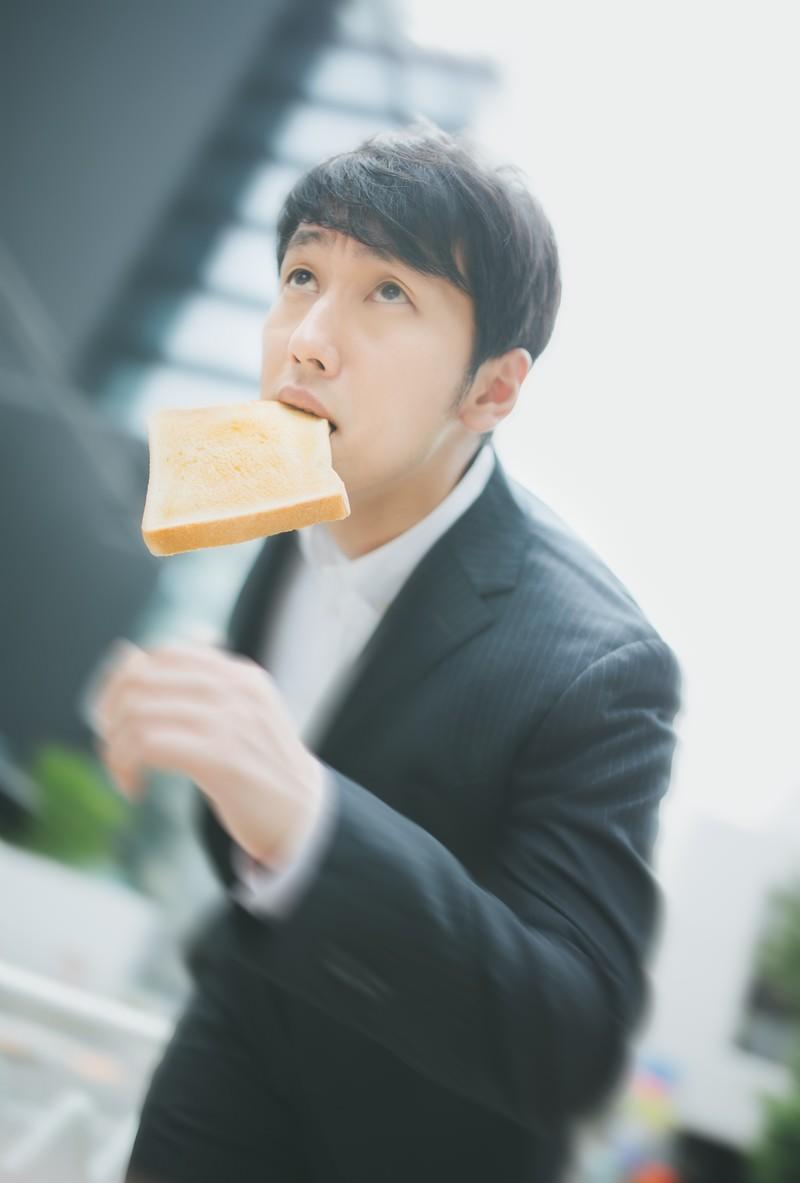 「トーストを咥え颯爽と出社するビジネスパーソン」の写真[モデル:大川竜弥]