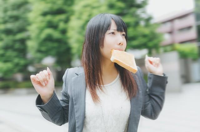 トーストを咥えて走る女性社員の写真