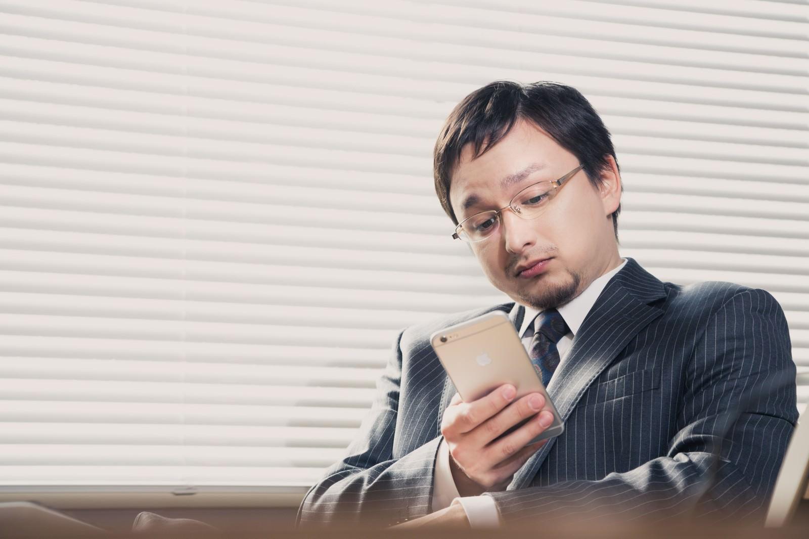 「業務中に平静を装いスマホでFX中の外資系サラリーマン」の写真[モデル:Max_Ezaki]