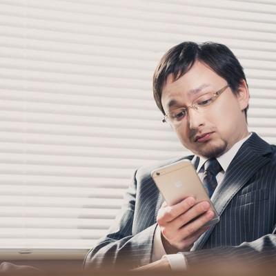 「業務中に平静を装いスマホでFX中の外資系サラリーマン」の写真素材