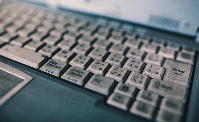 ひどく汚れたノートパソコンのキーボードの写真