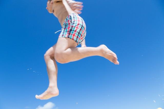 海開き飛び跳ねてではしゃぐ男子の写真