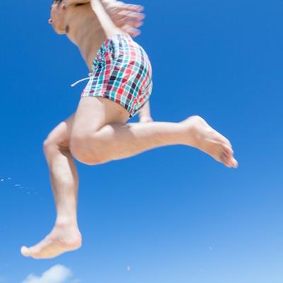 「海開き飛び跳ねてではしゃぐ男子」の写真素材