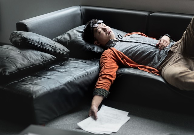 原稿を持ってソファーで寝落ちする担当の男性の写真