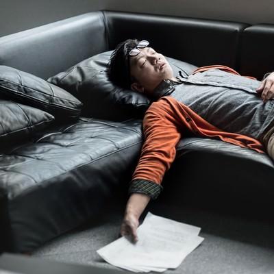 「原稿を持ってソファーで寝落ちする担当の男性」の写真素材