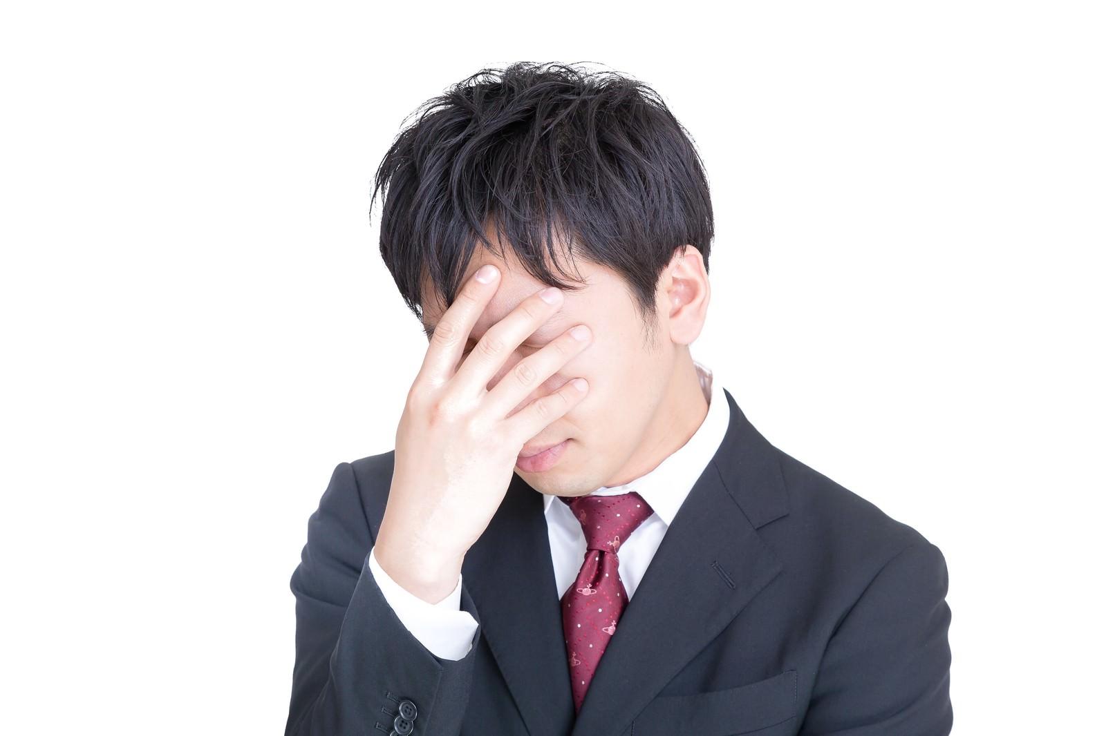 「頭を抱えてひどく落ち込む男性」の写真[モデル:大川竜弥]