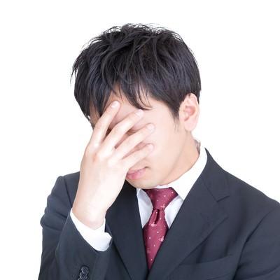 「頭を抱えてひどく落ち込む男性」の写真素材