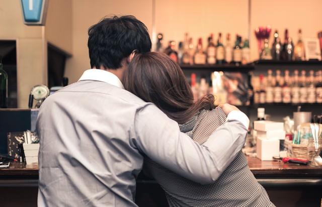 バーで寄り添うお忍びカップルの写真