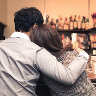 「バーで寄り添うお忍びカップル」の写真素材