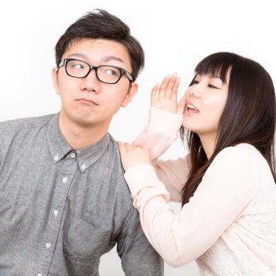 いいこと教えてあげるから耳を貸してと内緒話をする恋人の写真
