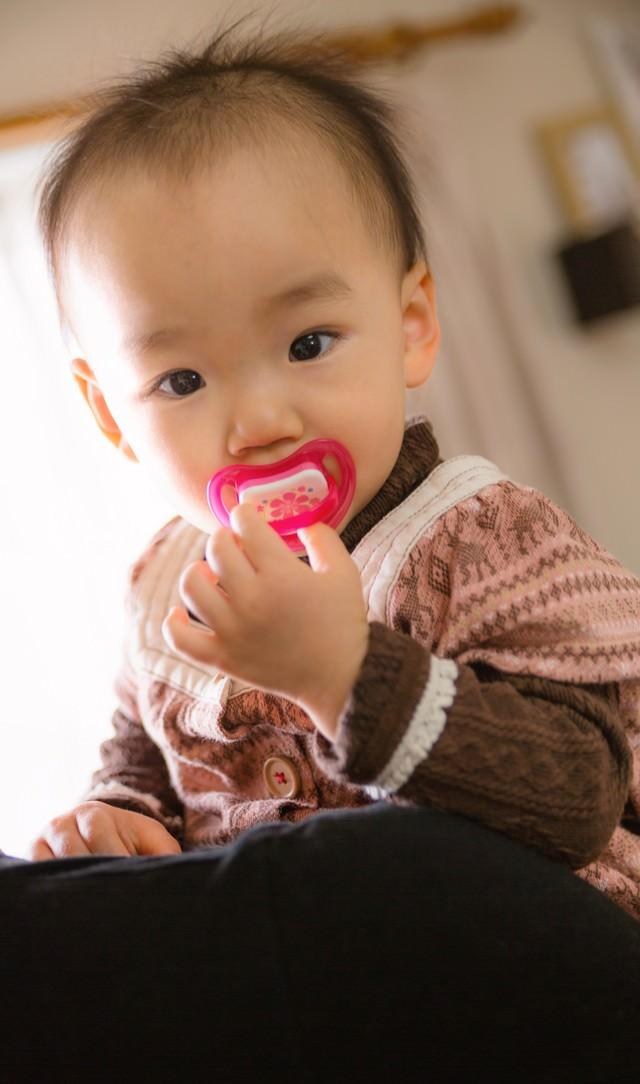 おしゃぶりを咥えた抱っこされる赤ちゃんの写真
