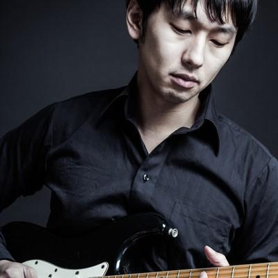 「黒いシャツと黒いギターでコーディネートするミュージシャン」の写真素材