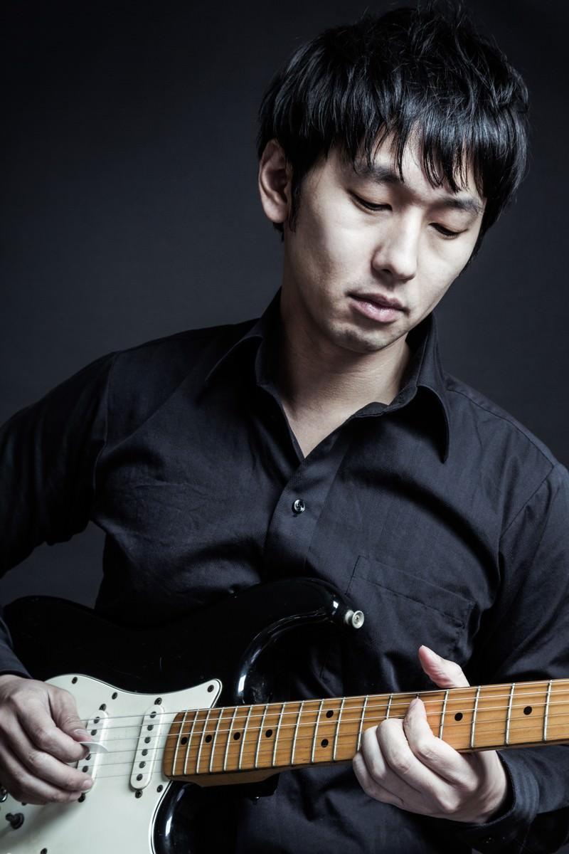 「黒いシャツと黒いギターでコーディネートするミュージシャン」の写真[モデル:大川竜弥]