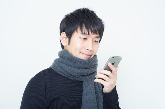 恋人からのメッセージを確認するマフラーを巻いた男性の写真