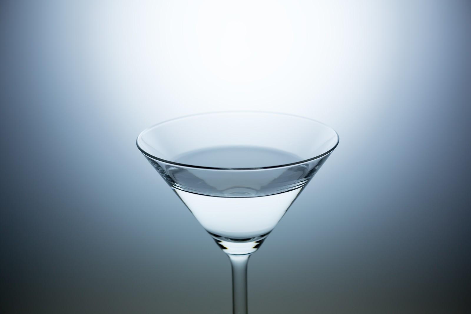 「水(酒)が入ったカクテルグラス」の写真