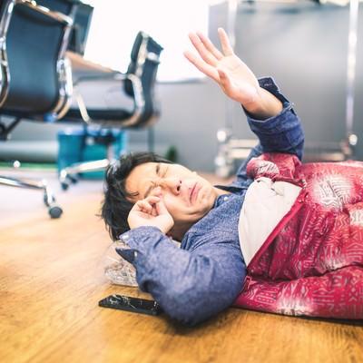 「朝、出社したら徹夜明けの上司が眠い目をこすっていた」の写真素材