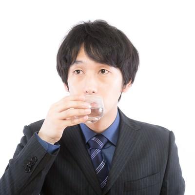 質疑応答の合間にのどを潤す男性の写真