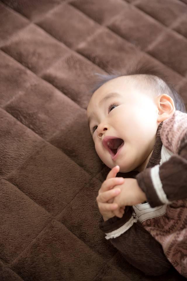 横になってママを呼ぶ幼児の写真