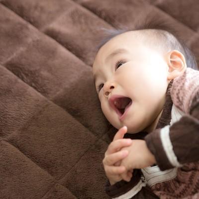 「横になってママを呼ぶ幼児」の写真素材