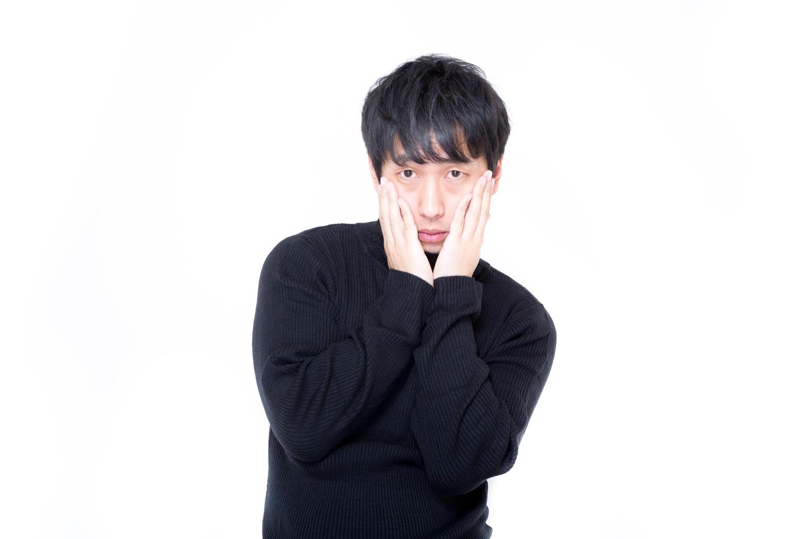 「両手を頬に心配そうな表情で見つめる男性」の写真[モデル:大川竜弥]
