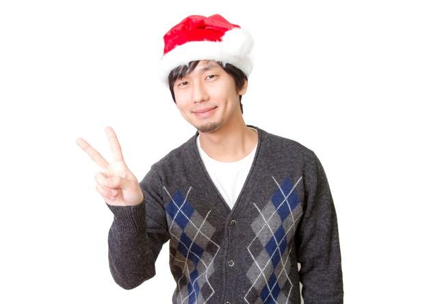 サンタ帽をかぶってピースする男性の写真