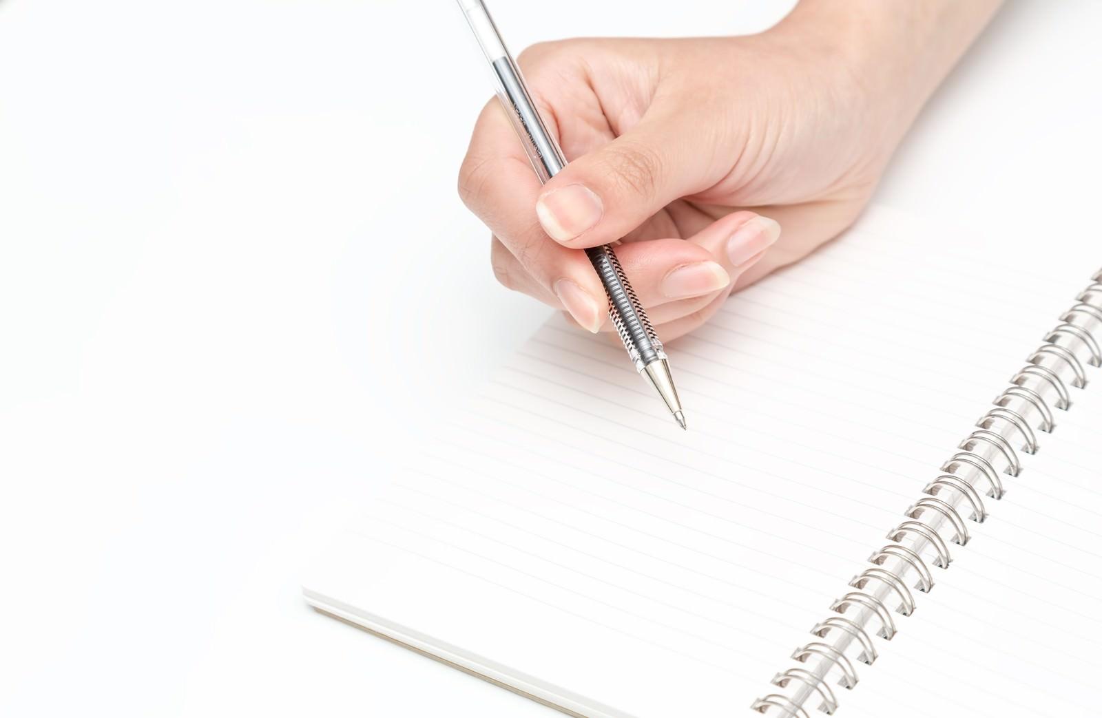 「ペンを握る手とノート」の写真
