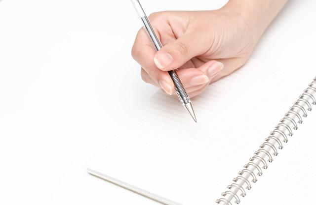 ペンを握る手とノートの写真