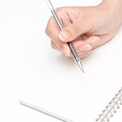 「ペンを握る手とノート」の写真素材