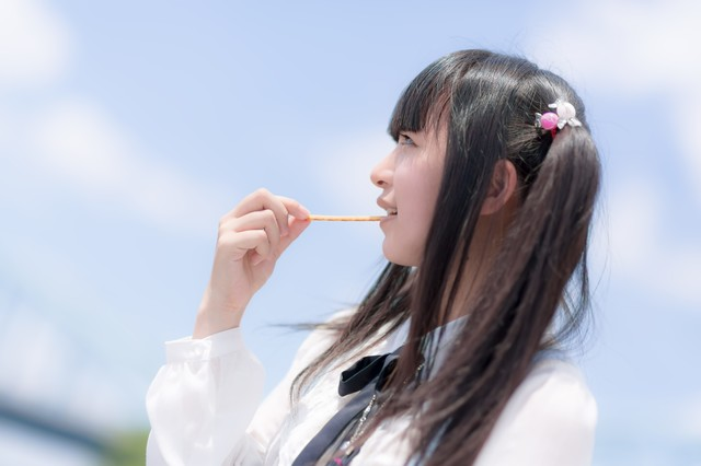 お菓子を食べるツインテールの女の子の写真