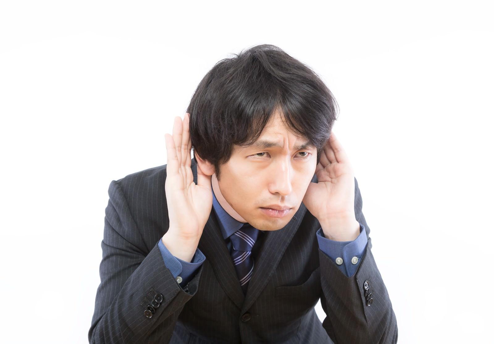 「具体的な追求をされると聞こえないふりをする男性」の写真[モデル:大川竜弥]