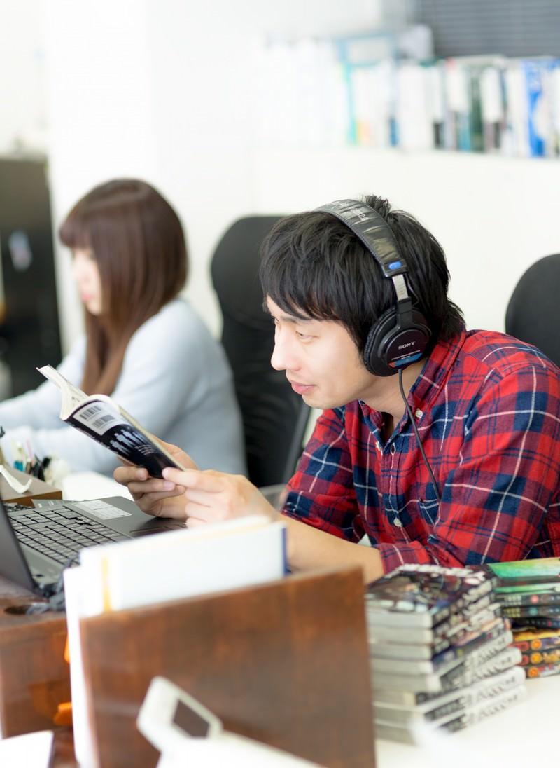 「職場で漫画を読みながら仕事をするエンジニア」の写真