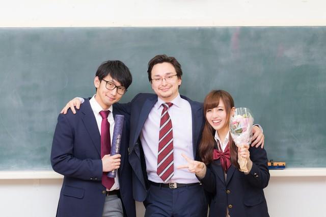 教え子の卒業を見届け感無量の担任教師の写真