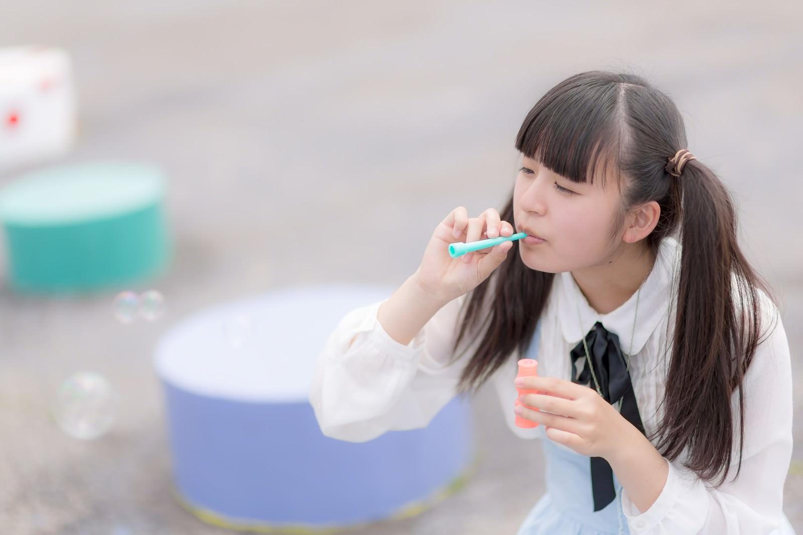 「公園でシャボン玉を吹くツインテールの女の子」の写真[モデル:こころ]