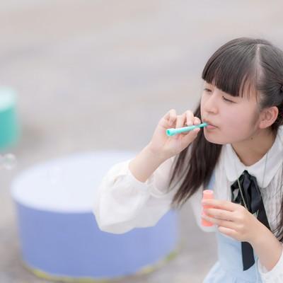 「公園でシャボン玉を吹くツインテールの女の子」の写真素材