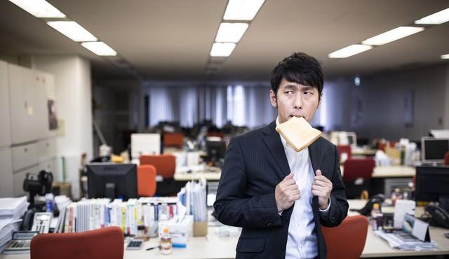 残業中トーストを食べ気合を入れる新卒社員の写真
