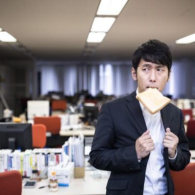 「残業中トーストを食べ気合を入れる新卒社員」の写真素材