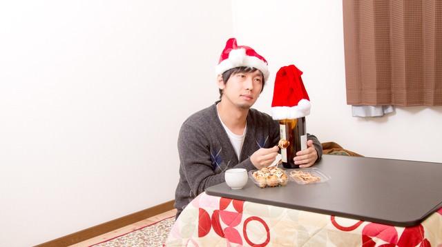 コタツで寂しくクリスマスを過ごす男性の写真