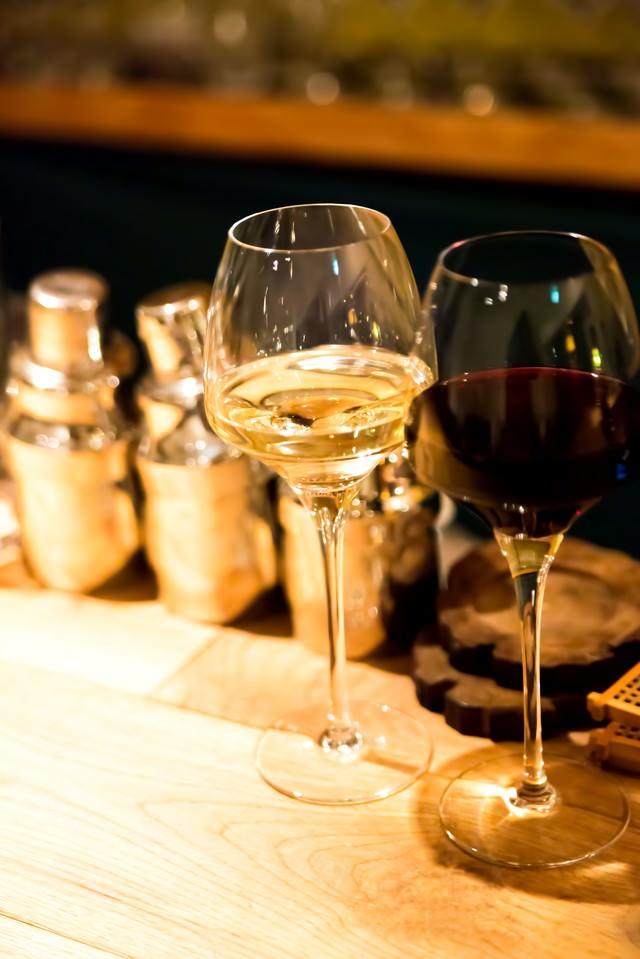 バーカウンターの白と赤のワインの写真