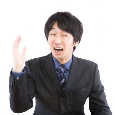 泣きながら右手を挙げる男性の写真